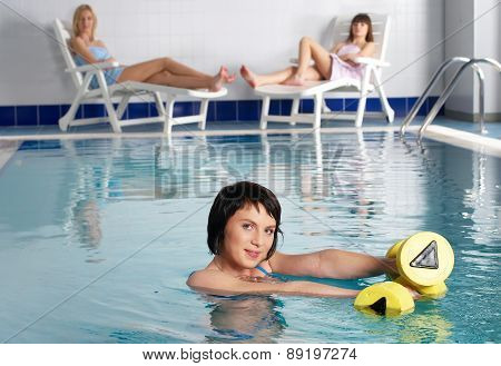 Young attractive woman in pool doing exercise