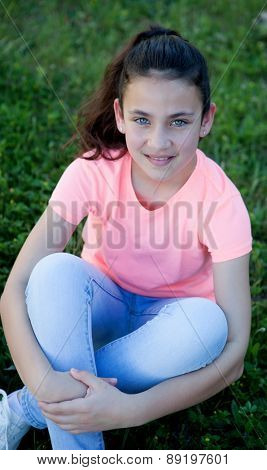 Beautiful preteen girl with blue eyes sitting on the grass