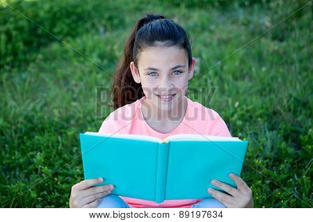 Beautiful preteen girl with blue eyes reading a book sitting on the grass