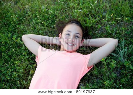 Beautiful preteen girl with blue eyes lying on the grass