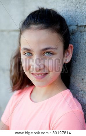 Portrait of a beautiful preteen girl with blue eyes outside