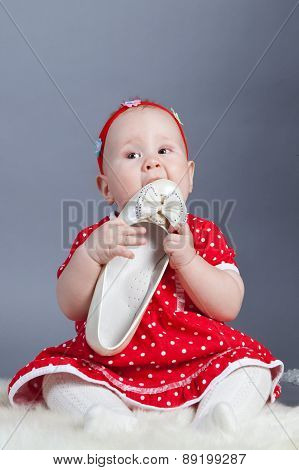 Small Girl In  Red Dress Holding Shoe