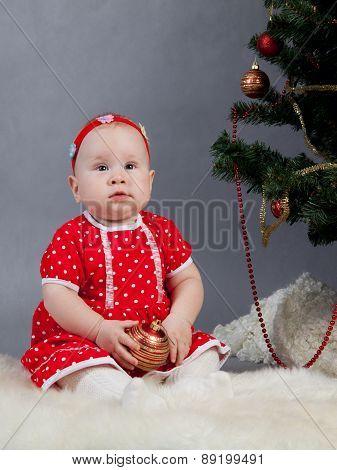 Little Girl In Red Dress Sitting Near Christmas Tree