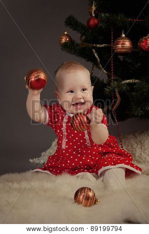 Little Girl In Red Dress Sitting Near Christmas Tree