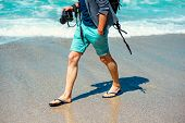 stock photo of short legs  - Man in shorts walking with photo camera on the beach - JPG