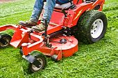picture of grass-cutter  - Man on a riding lawn mower that has grass stuck to the wheels - JPG