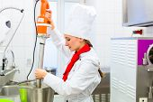 stock photo of food processor  - Female Chef preparing ice cream with food processor in gastronomy parlor kitchen - JPG