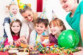 image of party hats  - Children at birthday party grabbing muffins and cake - JPG