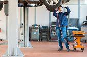 stock photo of car repair shop  - Mechanici changing car wheel in auto repair shop - JPG