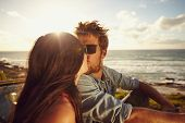 stock photo of romantic  - Affectionate young couple kissing at the beach - JPG