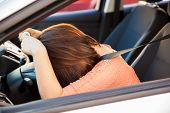 foto of upset  - Upset and stressed brunette leaning on the steering wheel of a car - JPG