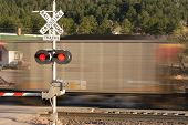 picture of railroad car  - Motion blurred locomotive at railroad crossing with signal box - JPG