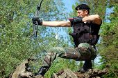 picture of bow arrow  - The soldier shoots with bow and arrow in the forest - JPG