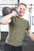 pic of kettlebell  - Young attractive man trains with kettlebell at a fitness gym center - JPG