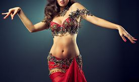 pic of belly-dance  - Beautiful girl with great body dances the dance of the belly  in Red shiny costume - JPG