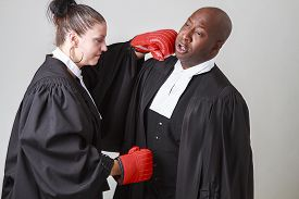 picture of toga  - caucasian woman wearing a lawyer toga punching a black man wearing a lawyer toga - JPG