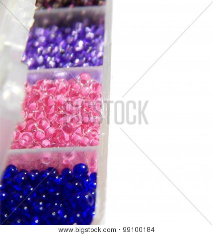 Blue, pink, lilac beads in boxes on a white background, closeup