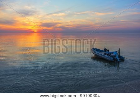 fishing boat in the calm sea on a background of a beautiful sunset with ships on the horizon