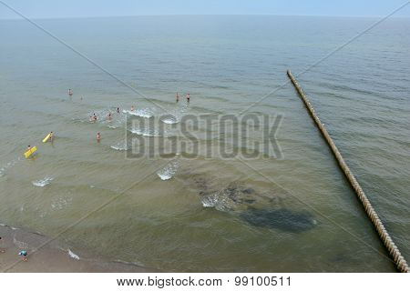 Wooden Groyne And People Bathing In The Sea In Trzesacz, Poland.