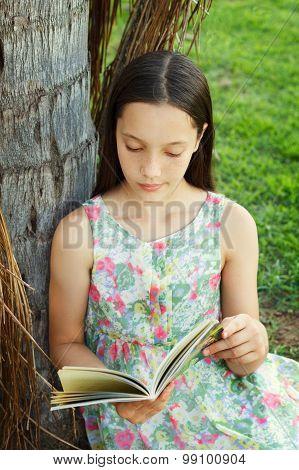 Cute Teen Girl Reading Book Sitting On Green Grass