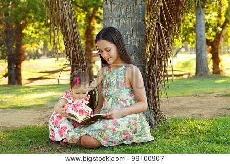 Cute Sisters Teen And Baby Girl Reading Book