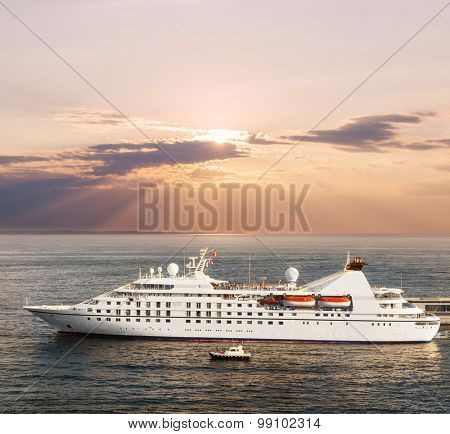 Small luxury cruise ship leaving port at sunset