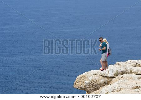 Two People Watching The Sea By A Rocky Precipice