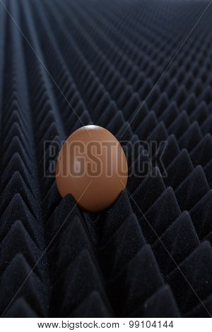 One Egg On Abstract Bumpy Black Background With Perspective