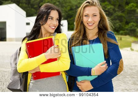 Two beautiful teenage students walking and smiling