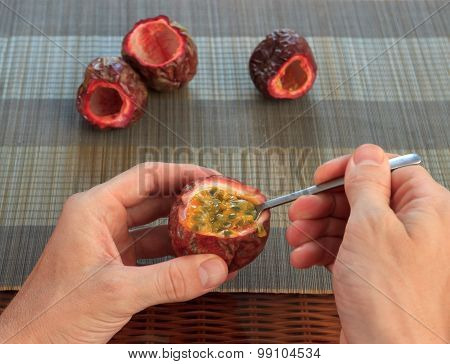Male Hand Scooping Out Passionfruit Against Bamboo Mats