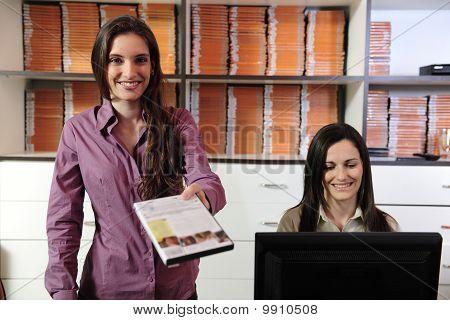 Women Handing Over Dvd At The Video Rental Store