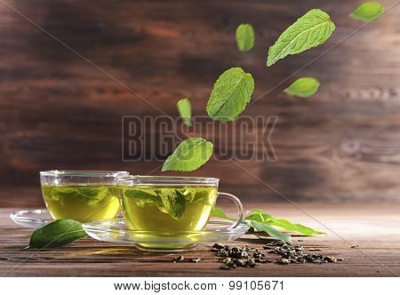 Mint leaves falling in cups of green tea on wooden background