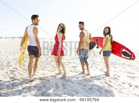 Group of friends walking together at the beach and holding surfboards
