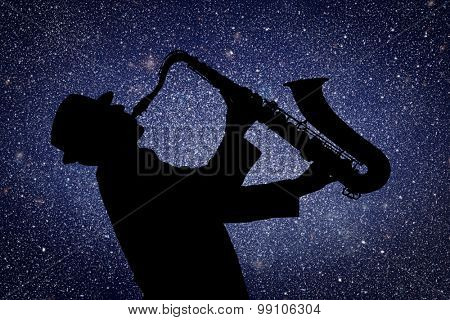 Saxophonist. Man playing on saxophone against the background of starry sky