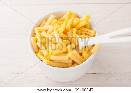 macaroni and cheese in a white cup