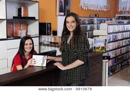 Employee Handing Over Dvd At The Video Rental Store