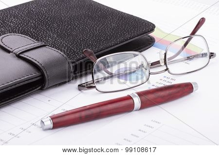 Business still-life of a charts pen eyeglasses card holder