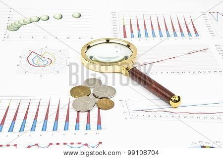 Business Still-life Of A Diagram, Magnifier, Coins