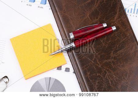 Business Still-life Of A Charts, Pen, Sticker, Card Holder