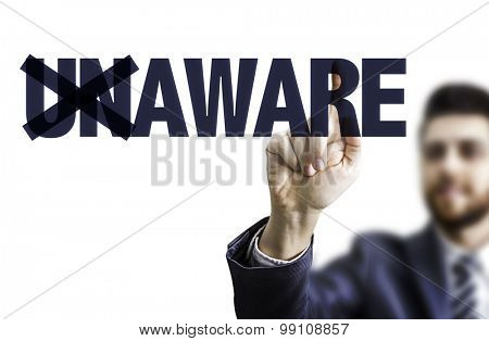 Business man pointing the text: Unaware/Aware