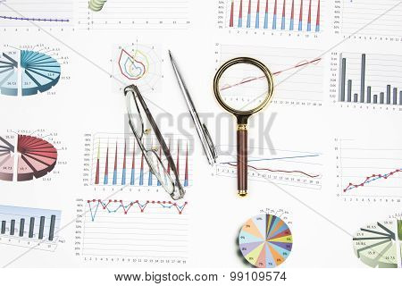 Business Still-life Of Graph, Eyeglasses, Magnifier, Shiny Pen