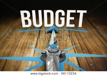 The word budget and compass against wooden table