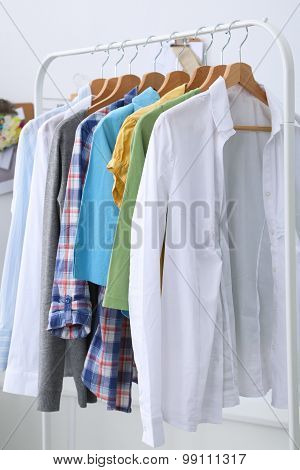 Clothes hang on a shelf in designer clothes store
