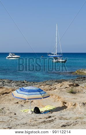 Umbrella On The Rocks On The Background Boats Moored In A Blue Sea