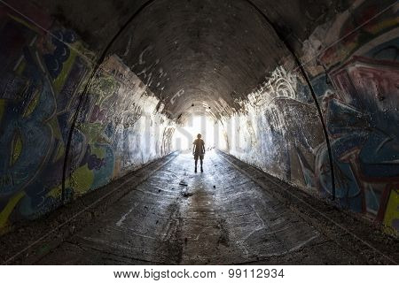 SIMI VALLEY, CALIFORNIA, USA - August 1, 2015:  Man exploring graffiti covered tunnel under the 10 lane 118 freeway near Los Angeles.