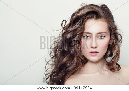 Portrait of young beautiful girl with clear skin and long healthy curly hair