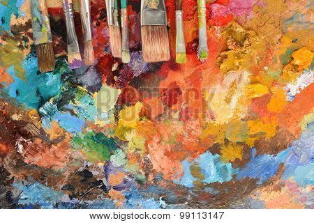Artist's paintbrushes on palette with various oil colors