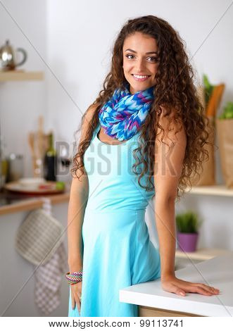 Young smilling woman standing in her kitchen