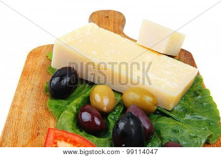 solid parmesan on wooden platter with olives and tomato isolated over white background