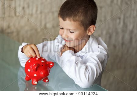 Little Boy Insert Coin Into Piggy Bank